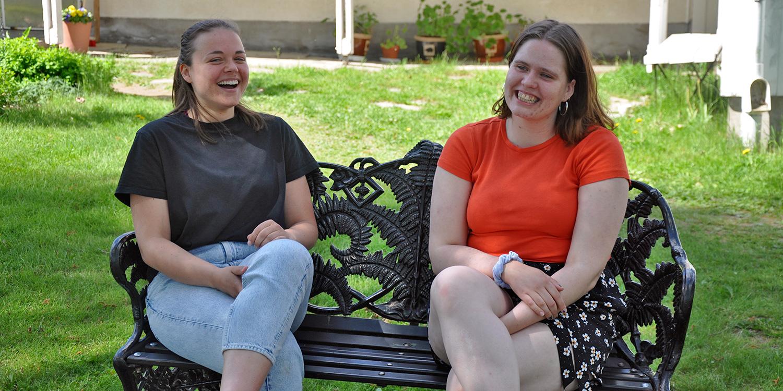 Två tjejer sitter på en soffa utanför skolan